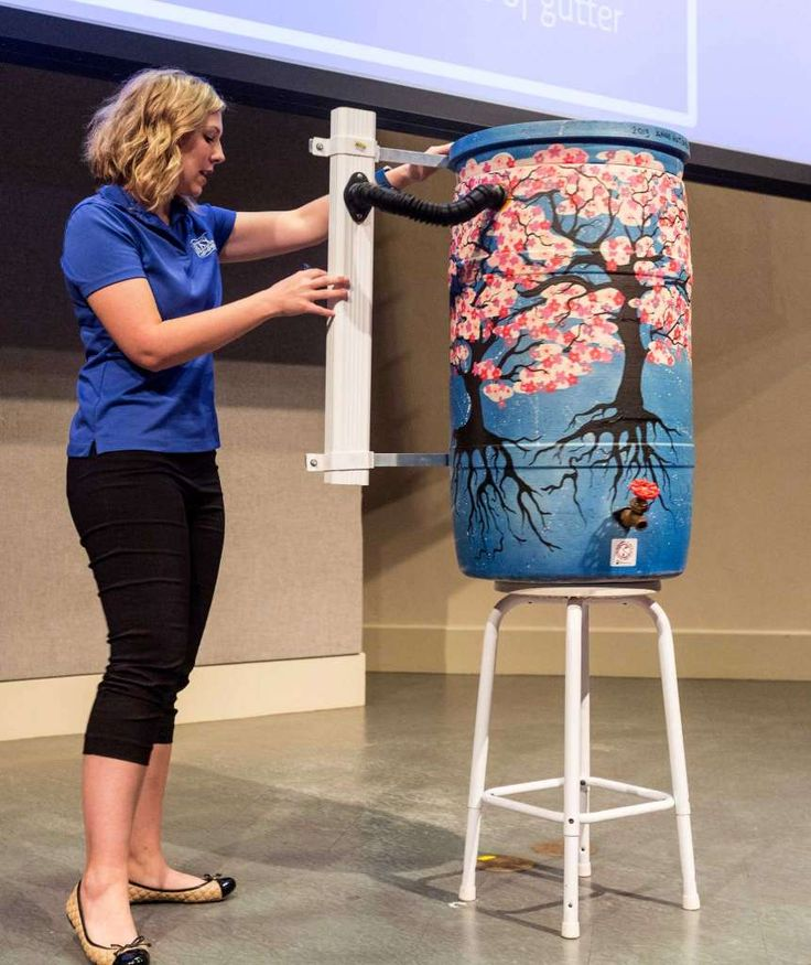 Sarah Cunningham, of the Galveston Bay Foundation, discusses how to connect a rain barrel to a rain-gutter downspout during a recent workshop.