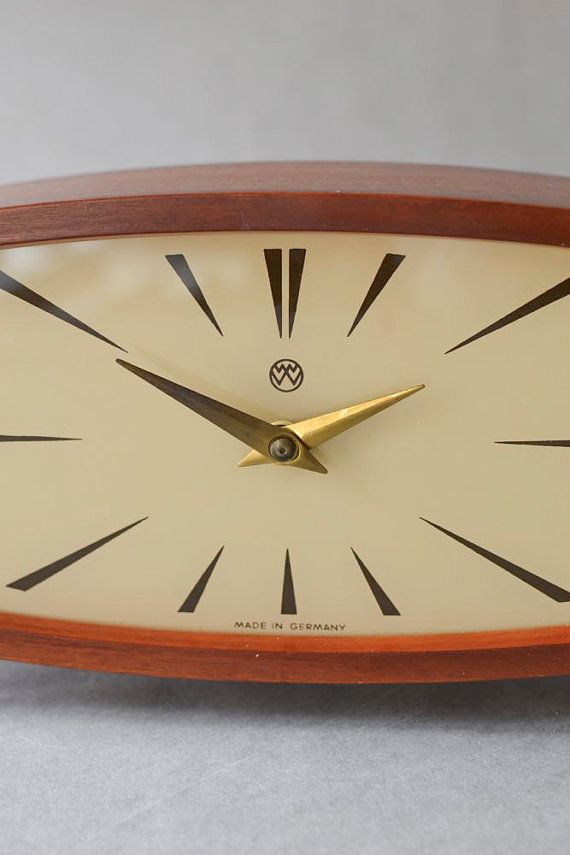 Vintage teak mantle desk clock / table clock by East German clockmaker Weimar. It is no secret that I LOVE Weimar clocks but this beauty here is really outstanding! It has teak, it has brass, it has tiny tapered legs. Everything the MCM lover needs. The clock face reads Made in Germany and above is the Weimar logo. The hands are made of brass. The clockwork was checked and is running on time This is a mechanical clock and has to be wound up. No battery required. Condition: very good ...
