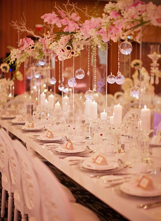 Centerpiece at an autumn winery wedding reception in california with candlelight for a dramatic, romantic feel. Table setting at a luxury wedding reception. Wedding decorations with flowers.