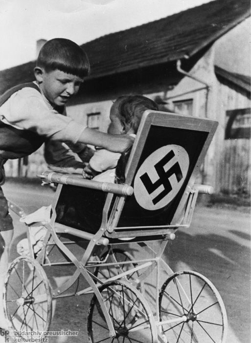 """""""Swastika Stroller in a Lower Bavarian Village (1937) When it came to Hitler portraits and other Nazi symbols, no article from everyday life was off-limits. Symbols of loyalty and unity were supposed to help Nazi propaganda to permeate all areas of life."""""""