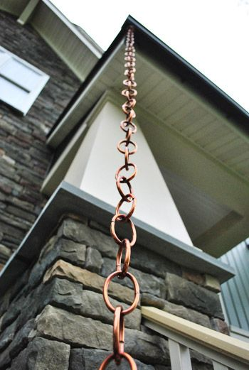 Rain Chains. Water hugs the chain going down to the ground, so you can remove a spout.