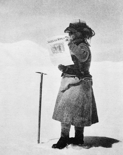 "Fanny Bullock Workman ( 8 January 1859 - 22 January 1925) was a geographer, cartographer and travel writer who not only was one of the first female professional mountaineers, she set several altitude records and championed women's rights.   Here she is holding up a newspaper that reads ""Votes  for Women""."