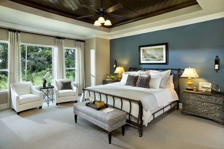 Not only does the greyish blue accent wall of this master bedroom chill the vibe, it also adds a lovely sense of dimension to the space.