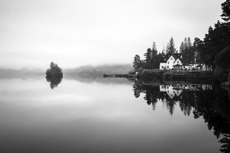 Scenic view of small wooded island, pier and house on loch, Loch Katrine, The Trossachs.