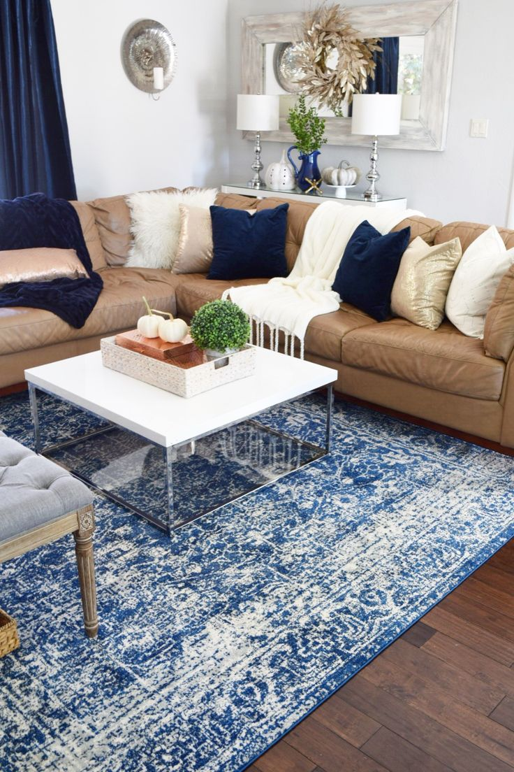A colorful area rug is grounded by neutral furniture and a mix of metallic  accessories to