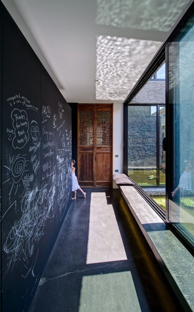 chalkboard doodle wall, concrete floor, sliding glass wall, pond, wooden chinese panels