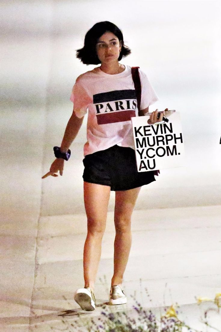 Lucy Hale wearing Silence + Noise Flowy Drawstring Shorts, Prada Trompe L'oeil Velvet Cahier Bag, Adornmonde Palmer Choker, Brandy Melville Paris Flag Shirt and Zcd Montreal Nico Sneakers