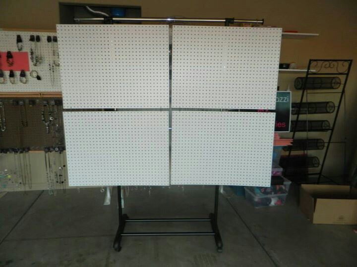 """This is just a clothing rolling rack from WalMart $14.99. Holding them on top are 4 shower curtain hooks and in the middle holding the 2 on bottom are """"S"""" hooks. The 4 peg boards came from only 1 sheet from Home Depot and had them cut it for us. Total cost for the display was about $35"""