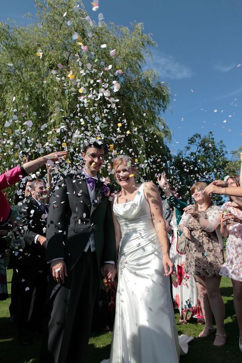 Throwing confetti over the bride and groom at a British wedding