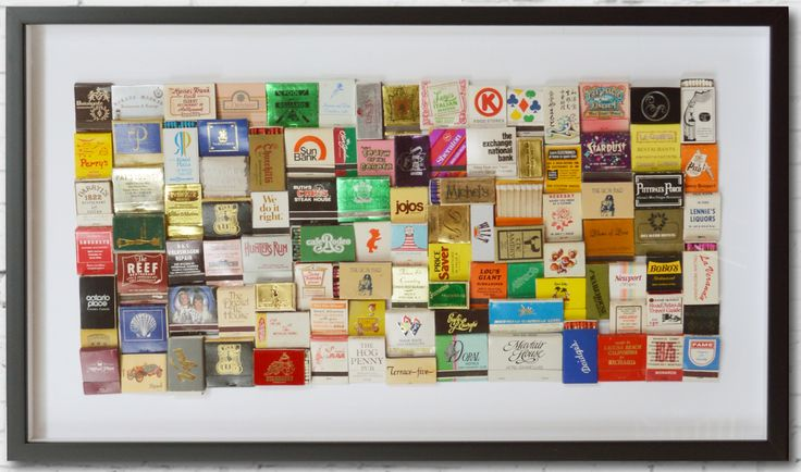 """Kolmiulotteinen kollaasiteos """"matches"""" vanhoista amerikkalaisista tulitikkuaskeista. 80 x 35 cm. Mustat vitriinikehykset. Sisustustaulu."""