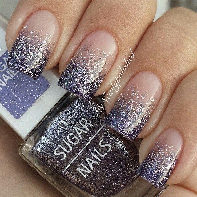 Elegantes uñas con las puntas en negro, decoradas con brillos plateados y cristalinos hasta la mitad de las uñas