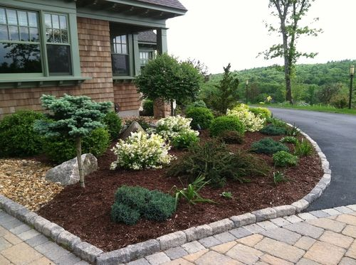 Cobblestone Edging Defines This Planting Front The