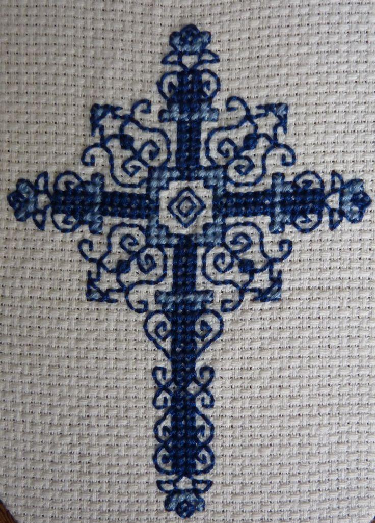 Cross stitch of a decorative cross.