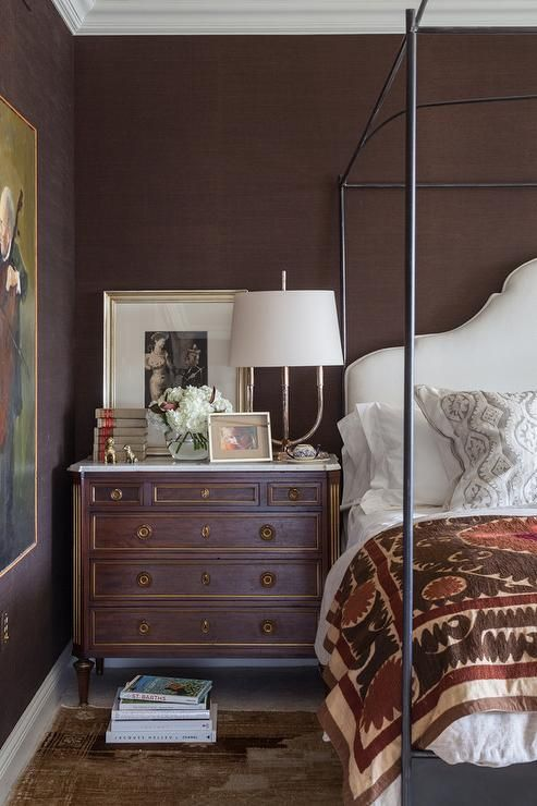 Chic Brown Bedroom Boasts Walls Clad In Brown Grasscloth Lined With An Iron Canopy Bed Dressed