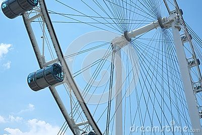 A dramatic rendition of the iconic Singapore Flyer, located in the Marina Bay waterfront of Singapore. The steel pylons of the structure are emphasized against a canvas of blue, moody clouds, which gives way to a burst of sun rays.