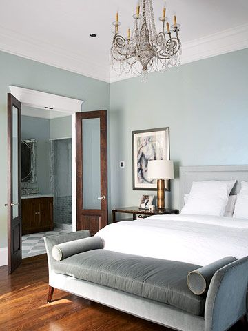 Modern Style ~ The gray-blue hue also works well in contemporary settings. In this bedroom, white moldings and bedding and dark-stained wood floors are neutral complements to the gray-blue walls. The light gray headboard with it square lines draws from the wall color. At the foot of the bed, a plush settee upholstered in dark gray brings an elegant touch to the otherwise minimal decor.