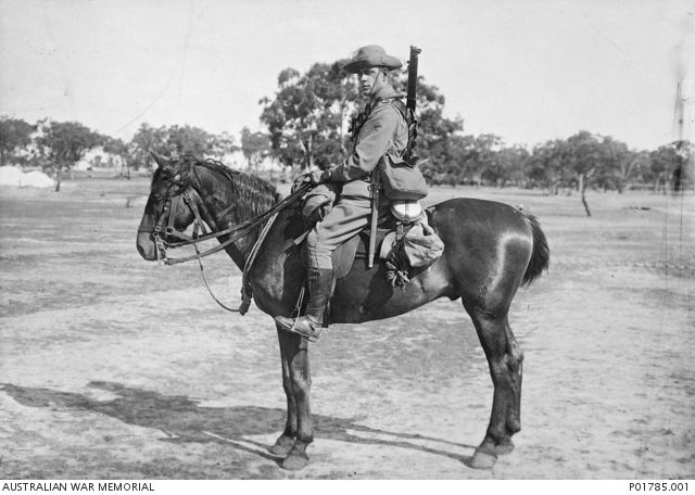 Melbourne, Vic, c. 1915-01. Portrait of 424 Trooper (Tpr) Ernest Stanley Impey, 9th Light Horse Regiment, 1st AIF, wearing full uniform and kit, mounted on his horse. Tpr Impey fought at Gallipoli, in the Middle East and in France, before being invalided out with the rank of Corporal in 1916-01. He returned to serve in France during 1917 and 1918 as a gunner with the 1st Divisional Ammunition Column. He was discharged in 1919. Ernest Impey died in 1978 at the age of 87