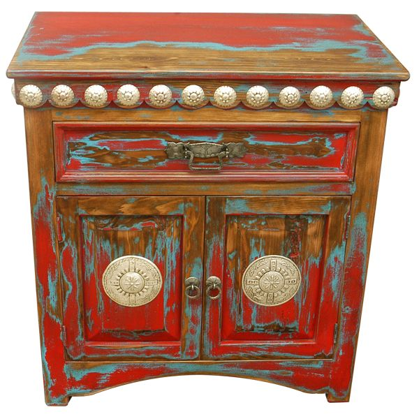 Beautiful western style end table with a faded red and blue turquoise finish. Rectangular open top, decorated on its sides through the use of hand hammered and hand tooled silvered conchos, the lower rim accompanying their curves. A standard drawer follows with a hand forged iron handle as also do underneath the two following wide doors finishing the facade. Each door bears a big hand hammered and hand tooled silvered concho in the central beveled sections. The bottom section is arch like…