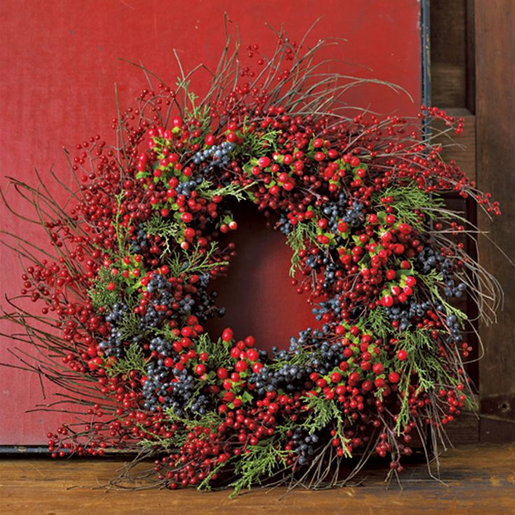 Door wreath made from berries. Very natural, rustic and homely looking. The violet makes the design look a bit more modern.