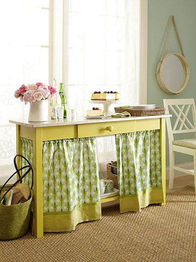 Make an adorable table skirt for any table or desk in your home by using a tension rod. Simply slide the curtain on the rod and then hang the rod up!