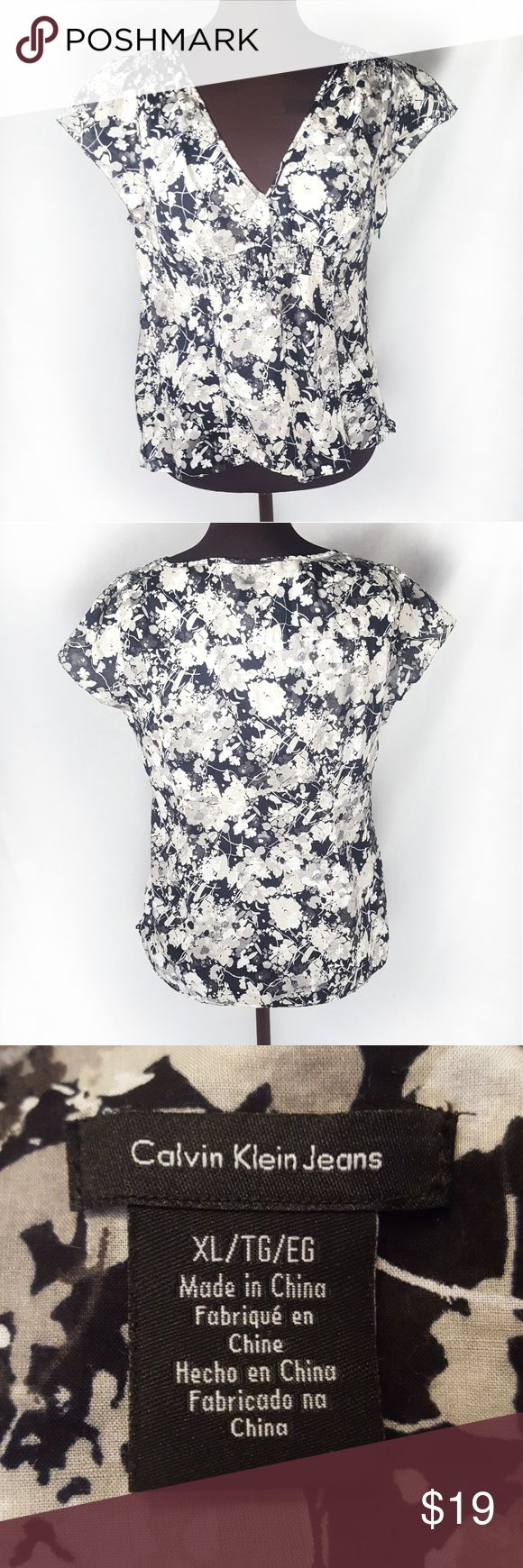 Calvin Klein Women's Blouse Top XL Cotton Floral Lovely cotton women's Top by Calvin Klein jeans. Women's size extra large. Flat underarm to underarm measurement is 20 in. There is smocking in the front for adjustability. The pattern is a floral with grey black and white. 100% cotton. There is a small mend one seam where it was coming undone at the bottom. Calvin Klein Jeans Tops Blouses