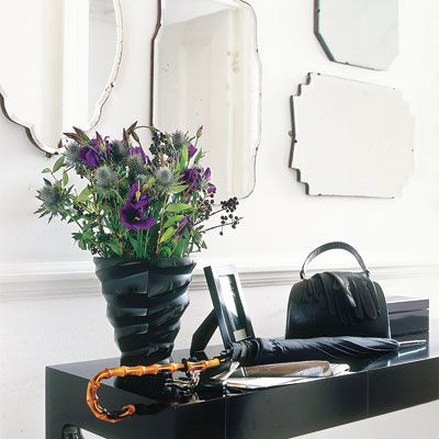 Maximize natural light in an entryway by decorating a wall with reflective frameless mirrors in different shapes and sizes.    Similar to shown: Husnes mirror, $30; Kolja oval mirror, $10; and Kolja round mirror, $15; ikea.com