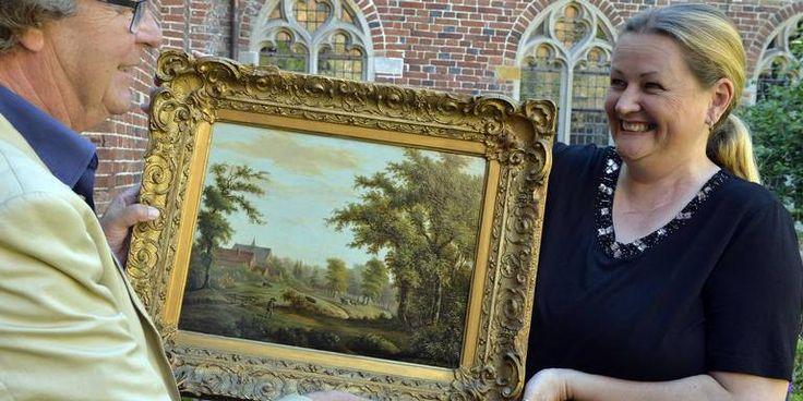 Directeur Margriet van Klinken en bestuurder Pim Witteveen van Klooster ter Apel geven het schilderij zijn plekje in de kapittelzaal.