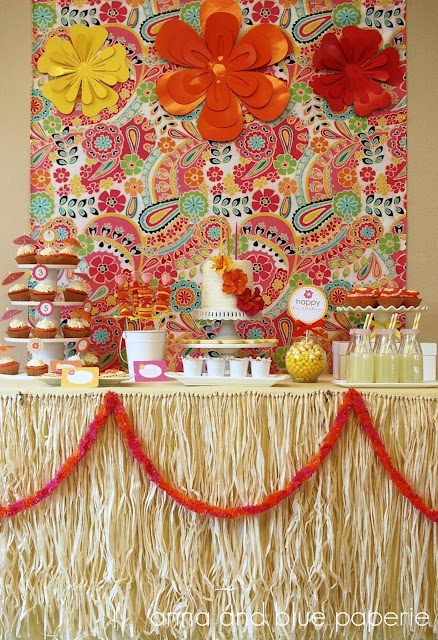 incorporated the hibiscus flowers and party color scheme throughout the dessert table.  A happy and colorful bed linen print with bright swirls of flowers and paisley, used as the backdrop for the dessert table.  The dessert table was adorned with large paper flowers that were added to the backdrop...