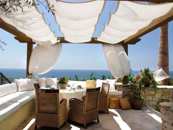 pergola en bois moderne avec rideaux blancs et un salon de jardin tressé