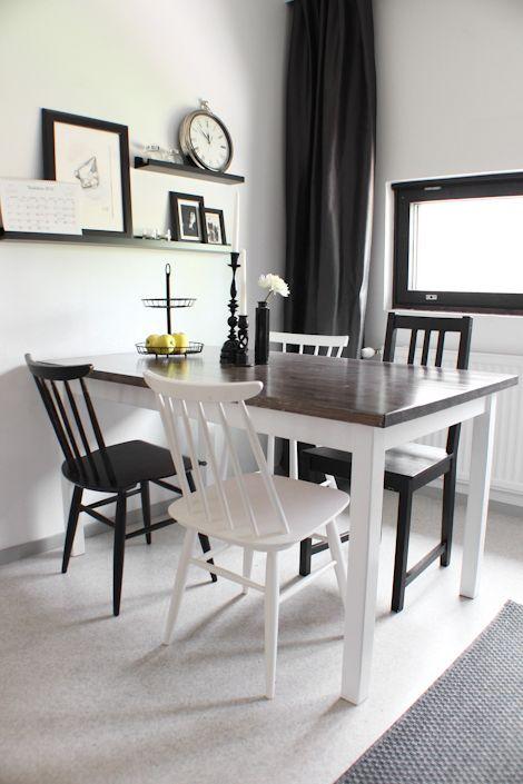 Table à manger en bois noire avec les pieds blancs et des chaises en noir et blanc