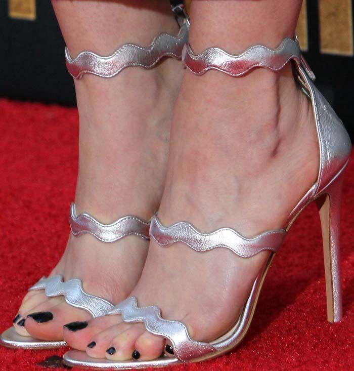 Emilia Clarke slips her feet into the triple-strapped wavy ...