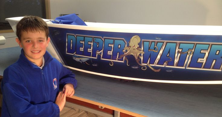"""Deeper Water is a Partial Wrap with an under water theme, custom made for Archer! Doesn't his Optimist Sailing Dinghy look cool? Archer named his boat after the Paul Kelly song """"Deeper Water"""" and wanted graphics to match the name. So we created an underwater theme for Archer with some fish and tough looking sharks swimming around on the hull of Deeper Water. www.optiwraps.com"""