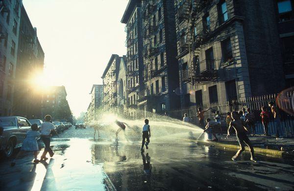 Une bouche d'incendie rafraîchit les jeunes durant une chaude journée à Harlem, New York (1977)