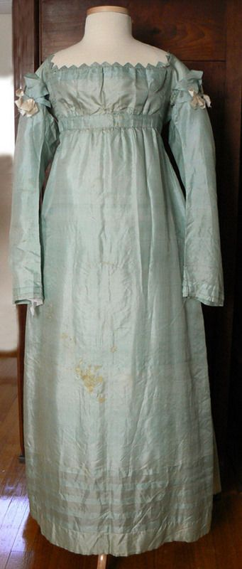 Genesee Country Village & Museum: 1815-1820. hand stitched icy green plain weave silk. It has a very high waist and very long tubular sleeves which would have been worn slightly ruched on the arm. The skirt is in 3 panels and slightly gathered in front and pleated in the back.  It has a Vandyked neckline of little triangular tabs in the sleeve, forming a gorgeous cap effect which is accented with little white ribbon bows.