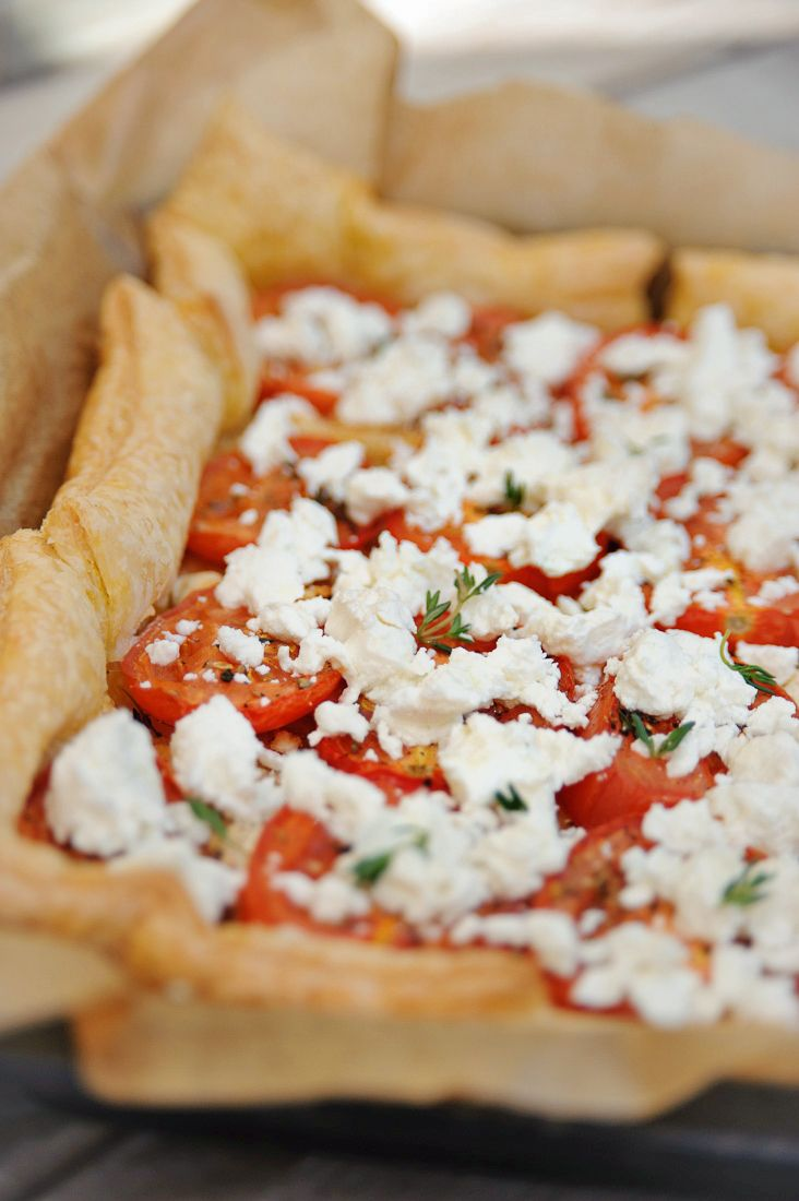 Bereiden: Verwarm de oven voor op 200°C. Leg het bladerdeeg op een bakplaat bekleed met bakpapier. Het deeg mag een beetje over de rand van de bakplaat uitkomen. Bestrooi het bladerdeeg met paneermeel. Leg hierop de uienringen, verkruimel de helft van de geitenkaas erover en beleg met tomaten.