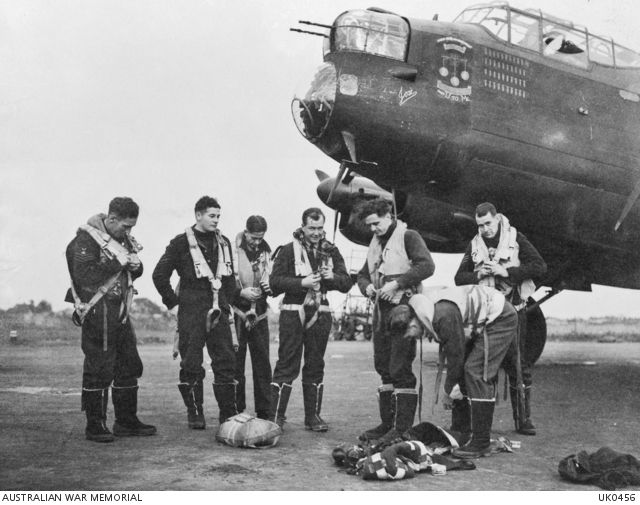 """Crew of """"M"""" for Mother, a Lancaster aircraft belonging to No. 467 Squadron RAAF in Bomber Command. The Squadron is based at RAF Station Waddington, and this crew is just preparing to take off on a raid over Berlin."""