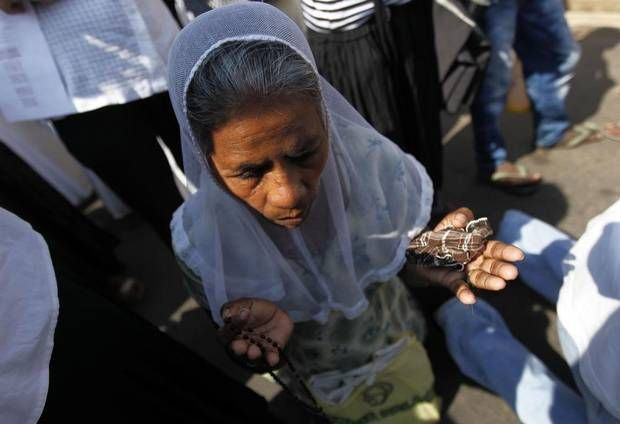 A Catholic woman prays during a special Good Friday mass at a church in Colombo