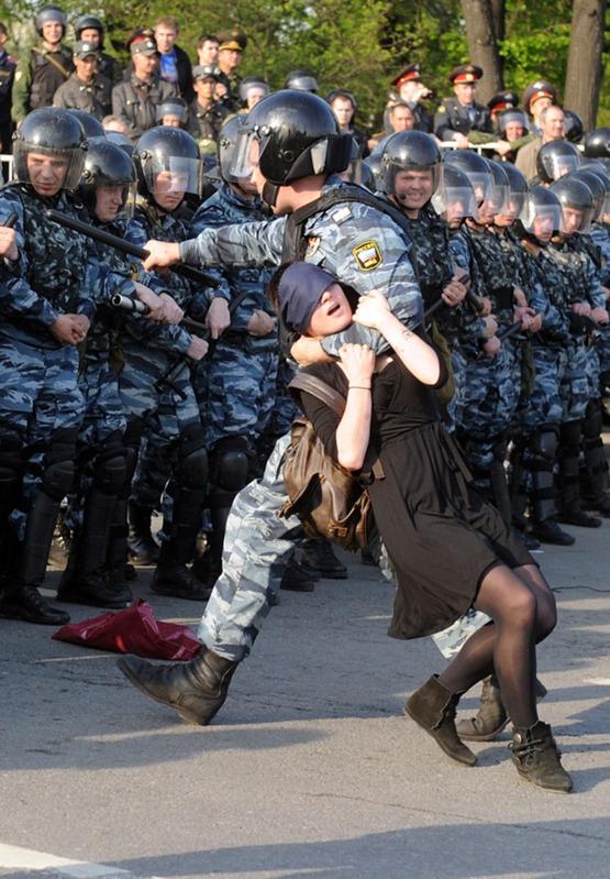 Moscú, 6 mayo 2012: Una joven es llevada semi-asfixiada por un policía antidisturbios, en medio de masivas protestas contra el gobierno de Vladimir Putin.