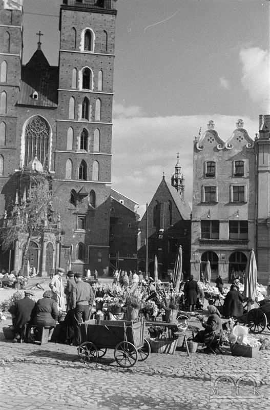 Rynek Główny, stragany, kamienica Czyncielów (nr 4), kościół Mariacki - fragment 2. połowa lat 40. XX w.