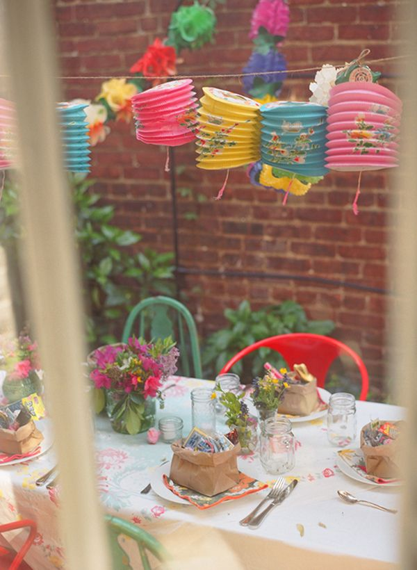 spring party ideas - table setting, lanterns, colorful chairs in backyard.