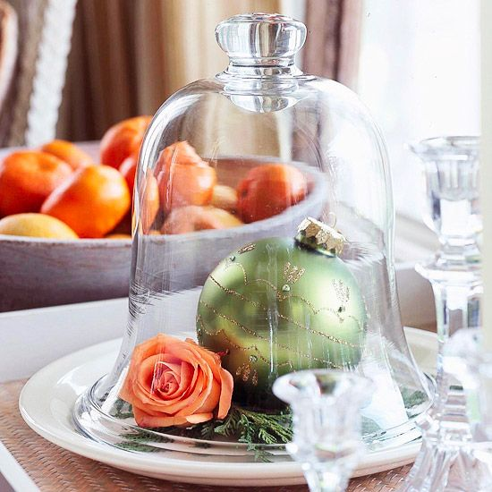 Under Glass:   A clear glass cloche on a platter or tray plays host to a few perfect decorations: one stunning holiday ornament, a few sprigs of evergreens, and a single perfect rose. Keep the rose fresh by inserting the stem into a florist's water tube, which can be concealed under the greenery.