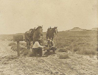 This picture was taken in 1908 in West Texas. The picture shows two cowboys reading their mail by an old mailbox.