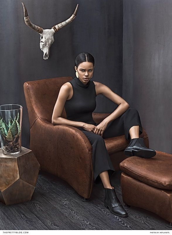 Modern black sleeveless outfit with short leather boots   Photograph by Weylandts  