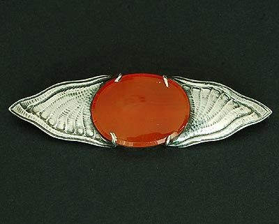 FONS REGGERS 1886-1962 - Oval silver brooch with hammered Amsterdamse School pattern and with oval cabochon cut cornelian fixed with claws pin with safety clasp the Netherlands ca.1925