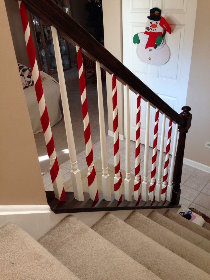Candy cane railings! Super cute & easy to do! Our spindles are white all ready so I just wrapped red ribbon around them. I taped the ribbon on the top & bottom.
