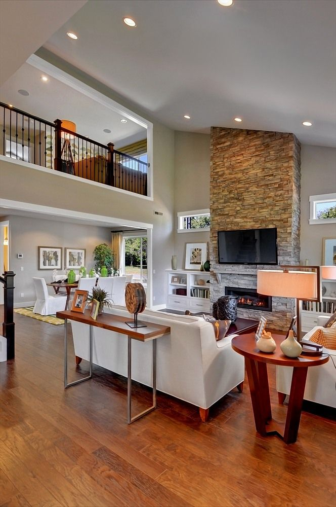 Vaulted, two-story living room. Balcony overlooking room. Two-story stone fireplace with mounted TV plus built in cabinetry/bookshelves.