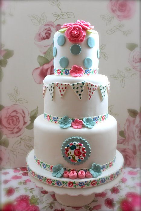 Cute 3 tier cake, With Polka dot top tier, hand cut and hand painted ditsy print bunting on the middle and a small hand painted rosette/plaque on the bottom tier…this cake was Inspired by the Cath Kidston ribbon I found in my drawer! :)