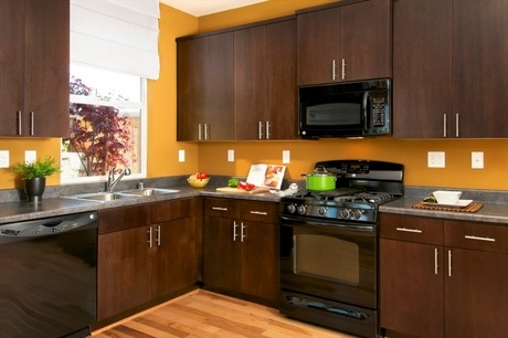 Sleek black appliances and polished aluminum handles for Brown kitchen cabinets with black appliances