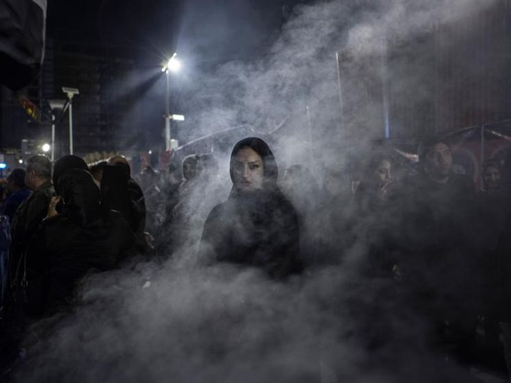 An Iranian woman walks through a haze of smoke caused by the burning of the herb