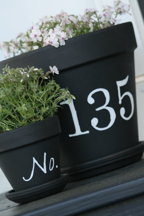 Front porch terra cotta pots painted with house numbers. Using flat black paint makes it look like chalkboard paint.